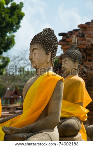 Two Buddha statues wrapped in an orange scarf. Ayutthaya city is the capital of Ayutthaya province in Thailand. - stock photo