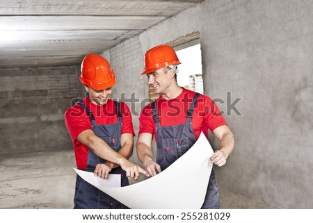 two builder engineer Architects working in empty concrete room  - planning and looking at blueprint hold in hands  Builder wear blue uniform and red hardhat shirt overall Man show in paper plan  - stock photo