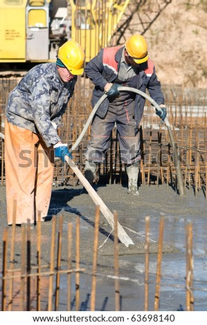 two builder workers during concrete works at construction site. Leveling and vibration - stock photo
