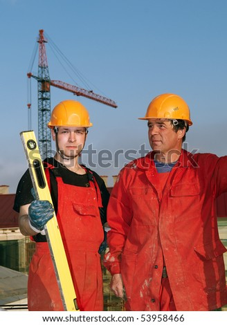 two builder workers in red uniform at construction site - stock photo