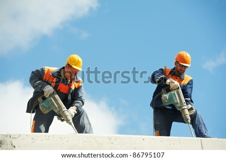 Two Builder workers with pneumatic hammer drill equipment at construction site - stock photo