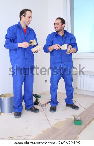 Two builders apply glue to the board for floor with a spatula in white room - stock photo