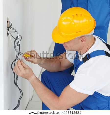 Two builders in helmets working with electricity indoors