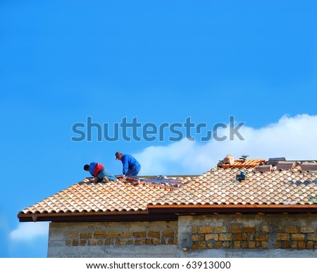 Two builders on the roof - stock photo