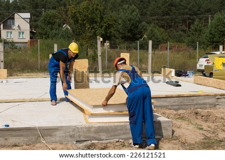 Two builders or construction workers handling insulated wall panels as they get ready to install them on the floor and foundation of a new build house - stock photo