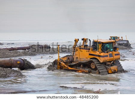 two Bulldozers on the beach on a dredging project in holland - stock photo