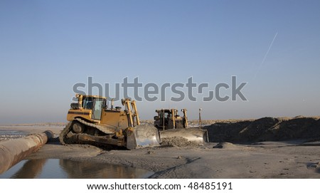 two Bulldozers on the beach on a dredging project in holland ready to start - stock photo