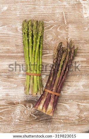 Two bunches of asparagus on wooden table