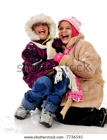 Two bundled elementary girls laughing in the snow.  Isolated on white. - stock photo