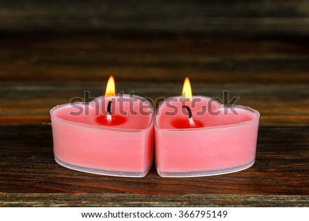 Two burning candles in the shape of a heart on wood close-up