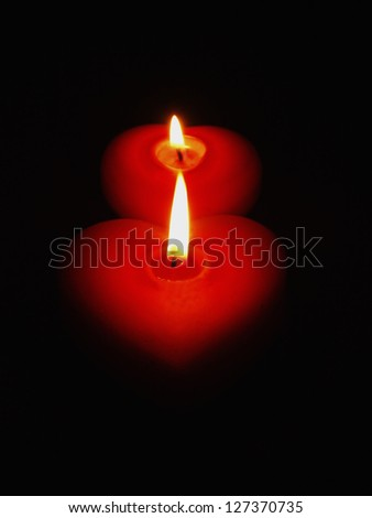 Two burning candles of red color in the form of heart.