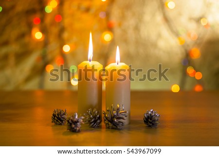 Two burning candles with forest, fir cones on a blurred background of lights and bokeh
