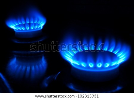 two burning gas burners, in the dark - stock photo