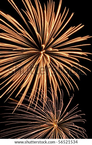 Two bursts of fireworks, the top reddish-yellow, the bottom silver with reddish-orange interior - stock photo