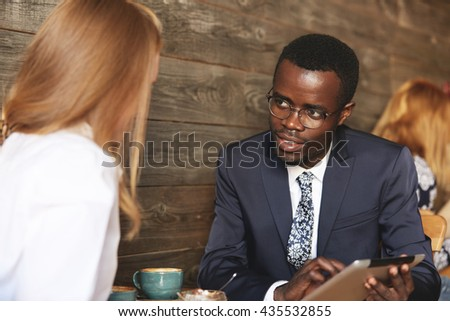 Two business associates of different races having a meeting at a cafe: young African man in formal suit and glasses showing a presentation to his redhead Caucasian female colleague on digital tablet - stock photo