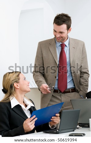 Two business colleague smiling and discussing at meeting in their modern office - stock photo