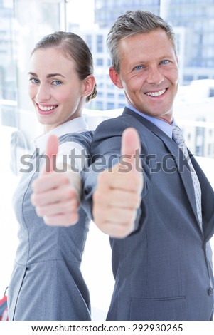 Two business colleagues giving thumbs up in the office - stock photo