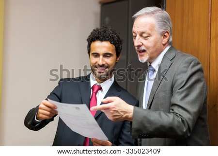 Two business colleagues reading a document in an office - stock photo