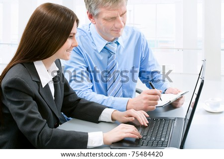 Two business colleagues sitting around table and working together. - stock photo