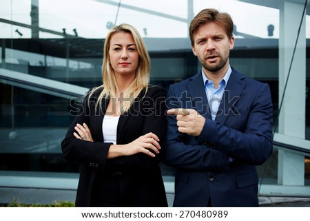 Two business colleagues standing against office building with crossed arms, experienced businessman friendly pointing with finger to his professional colleague while looking to you, teamwork concept - stock photo