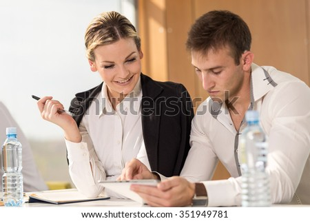 Two business colleagues working on a tablet computer in an office - stock photo