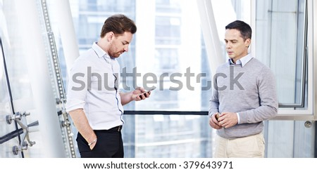 two business executives working together responding to a business situation. - stock photo