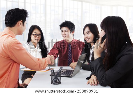 Two business leader shaking hands be witnessed by their team in a meeting, symbolizing a business cooperation - stock photo