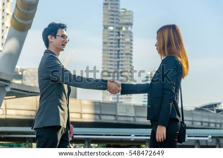 Two business man and woman shaking hands