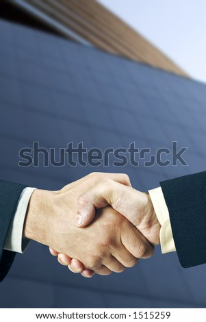 Two business man shaking hands in front of a modern building, nice light and depth of field.