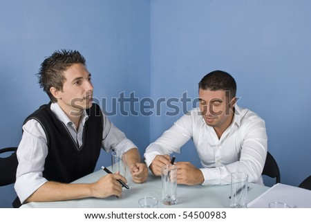 Two business man sitting on chair at a meeting,one of them speaking and the other listening him and smiling - stock photo