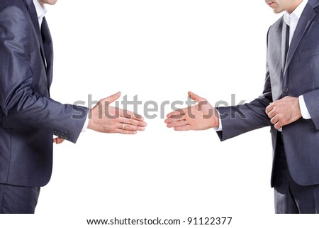 Two business men in a suit standing with his hand reaching for a handshake - stock photo