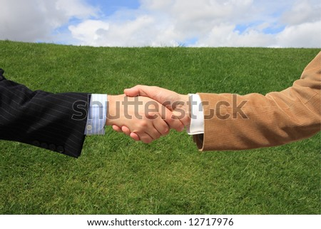 Two business men making a deal with a handshake at the field - stock photo