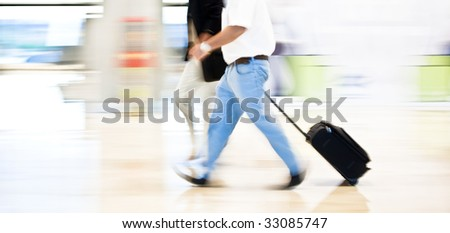 Two business men moving quickly on the terminal. Panning technique. - stock photo