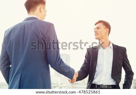 Two business men - partnership, shaking hands.