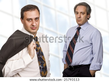 two business men portrait standing in front of a modern building