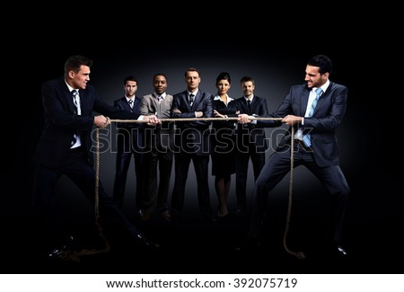 Two business men pulling rope in a competition. in the background is a group of business people - stock photo