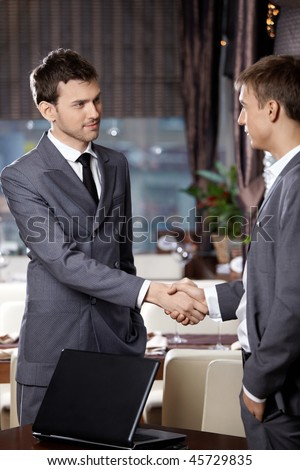 Two business men shake hands each other at a meeting at restaurant - stock photo