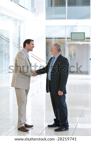 Two business men shaking hands in front of big glass window