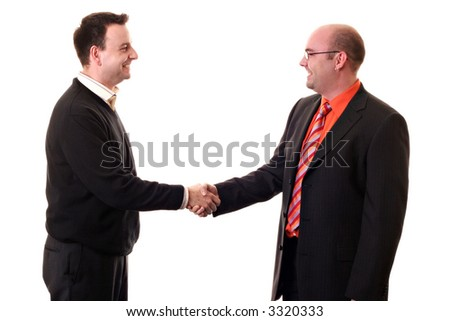 Two Business men shaking hands looking at each other. Smiling and wearing business suits - stock photo