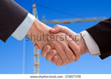 Two business men shaking hands on a background of crane - stock photo
