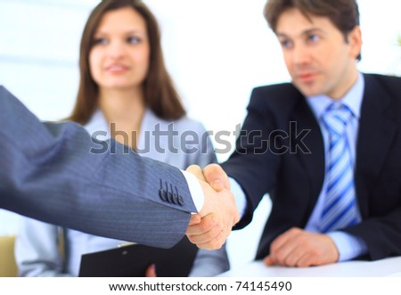 Two Business men shaking hands while team smiling at office - stock photo