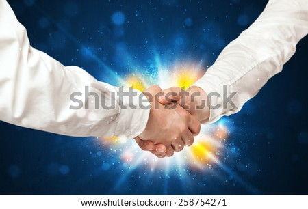 Two business men shaking hands with a successes agreement with explosion  - stock photo