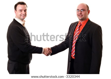 Two business men shaking hands with smiley faces and looking into the camera. - stock photo