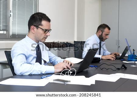 two business men working at pc in office - stock photo