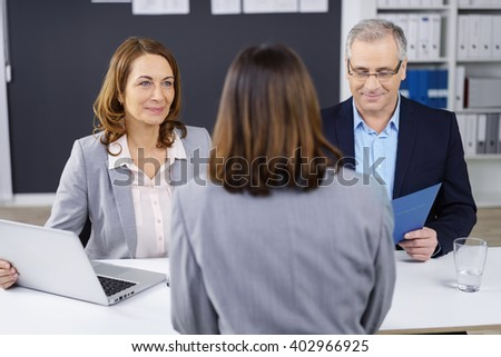 Two business partners, a stylish businessman and woman, conducting a job interview with a female applicant sitting with her back to the camera - stock photo