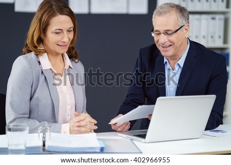 Two business partners, an attractive middle-aged man and woman, seated together at a desk discussing a document with a smile - stock photo