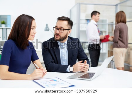 Two business partners discussing plans together at the table