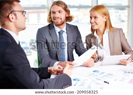 Two business partners listening to interviewee in office - stock photo