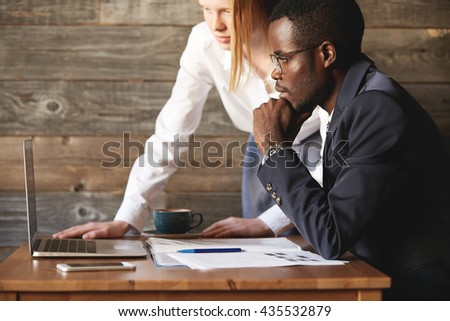 Two business partners looking at laptop screen indoors. African coworker sitting seriously with chin rested on hand. Caucasian colleague stands leaning on table with coffee, papers and devices. - stock photo