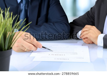 Two business partners signing a document